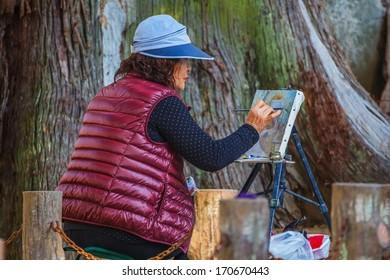 NARA, JAPAN - NOVEMBER 16: Senior Citizen in Nara, Japan on November 16, 2013. Unidentified old Japanese woman draws a gate of Tamukeyama Hachimangu in Nara Park