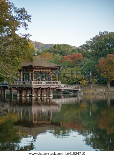 Nara, Japan - November 2, 2019: Ukimido floating pavilion reflecting in the lake in Nara deer park in autumn