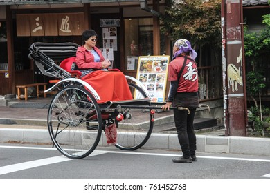 NARA, JAPAN - OCTOBER 18, 2017: Rikshaw with a lady client on the streets of Nara