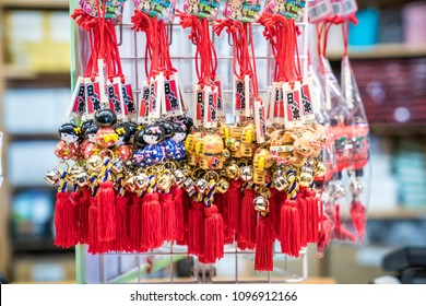 Nara Prefecture, Japan - 2 Mar 2018: Japanese amulet with bell; girl in blue and red yukata, gold cat, deer hang on to white grill for sales to tourist and visitor in Todaiji Temple, Nara, Japan.