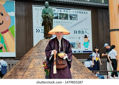 Nara,Japan,26 June 2016,Buddhist monk stand hold  folk metal bowl and rosary necklace next buddhist monk image at Nara street .