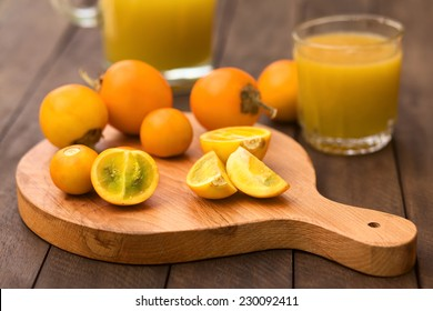 Naranjilla or Lulo fruits (lat. Solanum quitoense) on wooden board with freshly prepared naranjilla juice in the back (Selective Focus, Focus on the naranjilla pieces in the front)