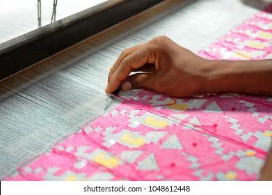 NARAYANGANJ, BANGLADESH - AUGUST 24, 2016: Handloom weaver weaves Jamdani saree on a traditional wooden hand weaving loom at Rupganj in Narayanganj, Bangladesh on August 24, 2016.