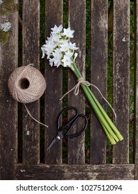 Narcissi flowers tied with twine, with a ball of garden string and scissors on a wooden slat background