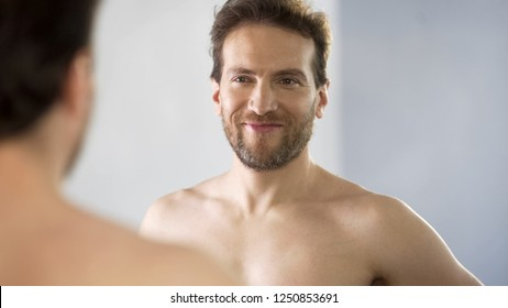 Narcissistic middle-aged man admiringly looking at his reflection in mirror