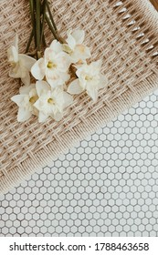 Narcissus flowers bouquet on rattan bench on mosaic tile. Minimal interior design concept.