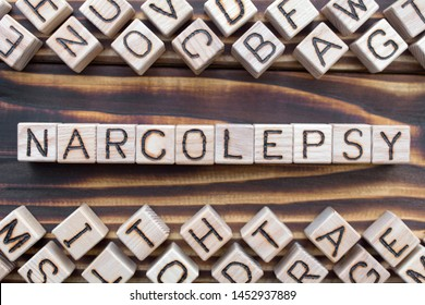 narcolepsy wooden cubes with letters, sleep disturbance  somnipathy concept, around the cubes random letters, top view on wooden background