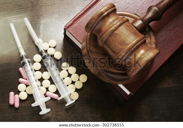Narcotics concept, judge's gavelon legal book with drugs and syringes on wooden table