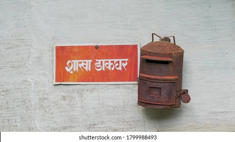 "Narda, Jharkhand / India - 09 August 2020: An old rusted Indian post box hanging on a wall. Translation: ""Post office"" written in hindi."