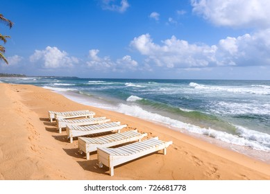 Narigama beach next to Hikkaduwa beach on west coast of Sri Lanka. Empty white wooden beach chairs on the sand with wild waves in the ocean and some leaves of palm trees near Hikkaduwa in Sri Lanka.