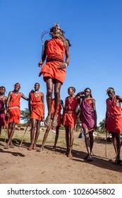 Narok, Masai Mara, Kenya, May 23, 2017: Masai warriors in traditional costume jumping during a ritual.