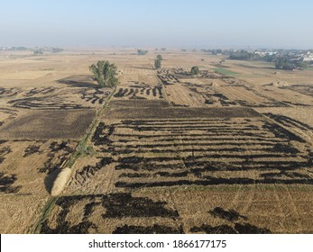 """""""Narowal, Pakistan - November 27, 2020: Burnt rice fields of a village after crop harvest, their burning causes smog in the vicinity and entire city of Lahore."""""""