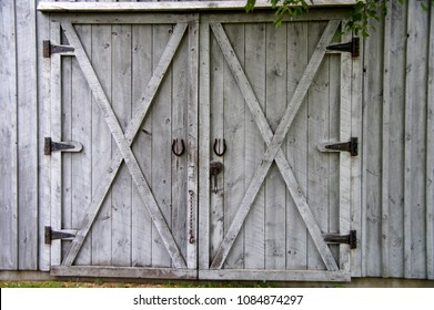 Narragansett, Rhode Island/USA- July 15, 2014: A horizontal black and white image of classic cross buck barn doors and iron hardware on a building at a historic working farm.