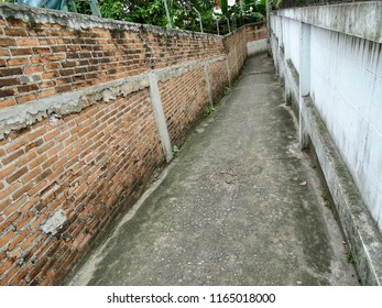 Narrow aisle. Old narrow corridor next to the park. Outside Bangkok Brick wall beside forest park. Thailand.