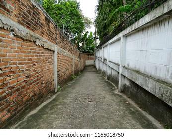 Narrow aisle. Old narrow corridor next to the park. Brick wall beside forest park.  Outside Bangkok Thailand.