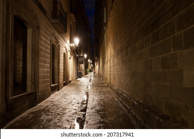 Narrow alley in the Gothic Quarter (Barri Gotic) of Barcelona at night in Catalonia, Spain.