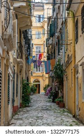 Narrow alley lined by old yellow buildings in Corfu, Greece
