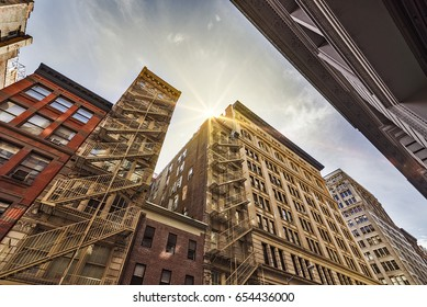 Narrow alley with Old apartment buildings and fire escapes on a sunny day in Midtown Manhattan, New York City