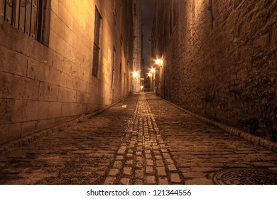Narrow alley in Old Montreal at night.