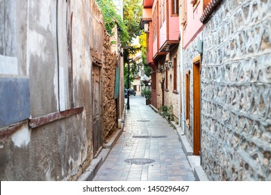 Narrow alley in the old town. Curved walls of houses in a narrow street. Old walls and doors in a narrow passage of a European small town