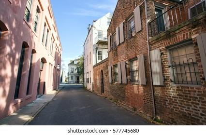 A narrow alley street runs through historic colorful houses in Charleston, South Carolina.