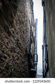Narrow alley way between two buildings, showing the ventilation pipes.