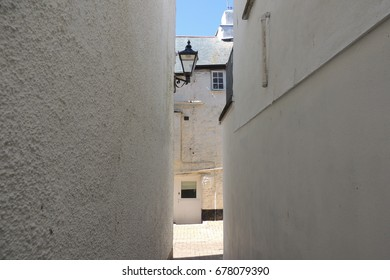 A narrow alley of white walls in the backstreets of Looe in Cornwall, with a shard of blue sky and sunshine gleaming above