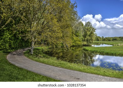Narrow asphalt road and canal curving thorugh a landscape with fields and forests in Biesbosch nature reserve in the Netherlands