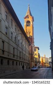 Narrow Asti street with belfry of Sanctuary of San Giuseppe, Piedmont, Italy