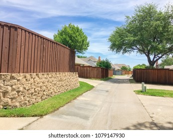 Narrow back alley at  suburban neighborhood in Irving, Texas, USA. Small concrete pathway leading to residential area with tree, wooden fence