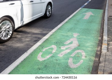 Narrow Bicycle Lane Marked in Green with Painted Symbols on the Right of a Busy Street