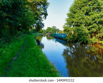 Narrow boats moored on the banks of the Shropshire Union Canal, near Whitchurch, in the late afternoon sunlight