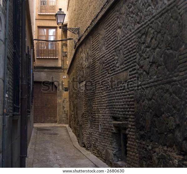 Narrow brick alleyway with lamp in historic center of Toledo, Spain
