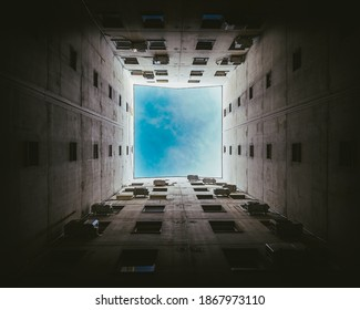 Narrow buildings well. Blue sky view above the roofs. Below view. Heaven view from the ground. Sky hole view.  Dramatic scene. Ghetto exit. Sky in the frame.