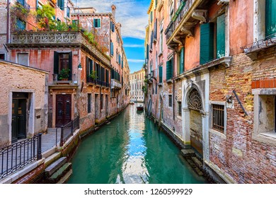 Narrow canal with boat and bridge in Venice, Italy. Architecture and landmark of Venice. Cozy cityscape of Venice.