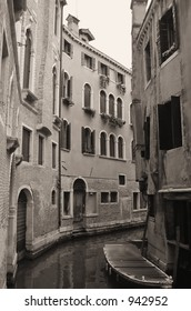 A narrow canal lined with homes in Venice - sepia toned.