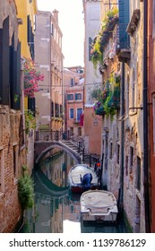 Narrow canal with motorboats and bridge, old historic buildings with flowers in Venice, Italy.