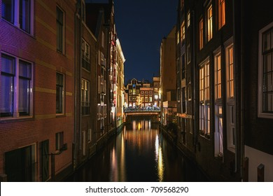 Narrow canal in the old town of Amsterdam in the evening