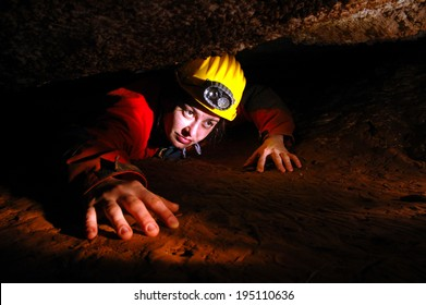 A narrow cave passage with a cave explorer