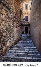 Narrow cobbled alley with stairs along medieval stone wall in Old Jewish Quarter - The Call in Girona city, Catalonia, Spain