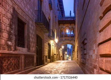 Narrow cobbled medieval Carrer del Bisbe street with Bridge of Sighs in Barri Gothic Quarter in the morning, Barcelona, Catalonia, Spain