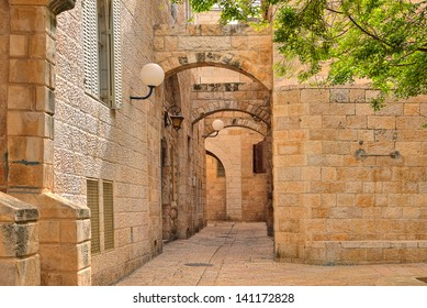 Narrow cobbled street among traditional stoned houses of jewish quarter at old historic part of jerusalem, Israel.
