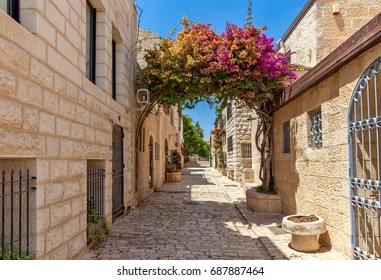 Narrow cobblestone street among stone houses in Yemin Moshe neighborhood in Jerusalem, Israel.