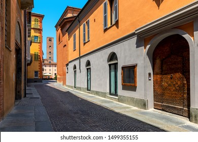 Narrow cobblestone street in front of old wooden door running towards medieval tower in small town of Alba in Piedmont, Northern Italy.