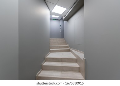 Narrow corridor with gray walls in an office center. Staircase in a narrow corridor leading upstairs.