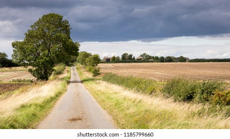 A narrow country lane runs through fields and farmland at Great Gidding, on the border of Huntingdonshire and Northamptonshire, in England's Midlands.