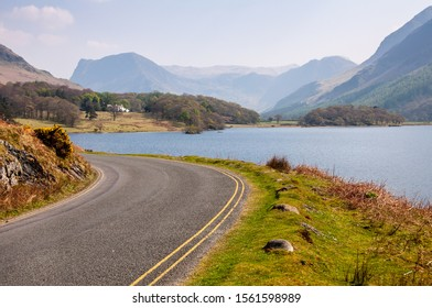 A narrow country lane winds around the shore of Crummock Water lake under the mountains of England's Lake District.