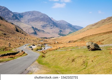 A narrow country lane winds through the valley floor of Honister Pass under the mountains of England's Lake District.