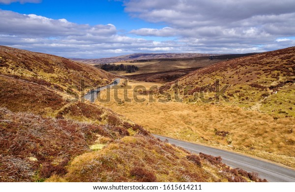 A narrow country lane winds through the deep valley of the Trough of Bowland under the hills of Lancashire in northern England.