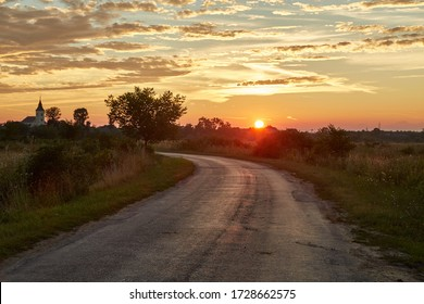 Narrow countryside road in sunset, approaching village
